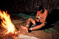 Tupi indian man works by firelight