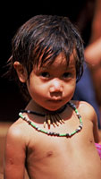 Tupi child wearing traditional Amazon seed bead necklace